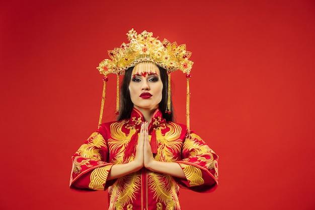 Mujer elegante tradicional china en el estudio sobre la pared roja
