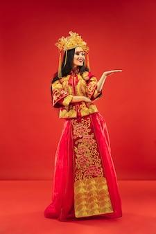 Mujer elegante tradicional china en el estudio sobre rojo.