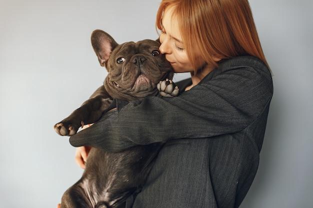 Mujer elegante en un traje negro con bulldog negro