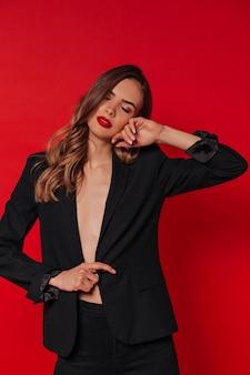 Mujer elegante en traje negro posando sobre pared roja posando con los ojos cerrados