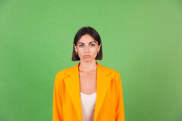 Mujer elegante en vestido beige de seda y blazer naranja de gran tamaño en verde, sonrisa infeliz hacia abajo, mira a la cámara con ojos tristes
