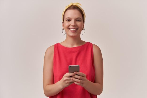 Mujer con elegante vestido rojo de moda y pañuelo amarillo con maquillaje natural y aretes posando en la pared mirándote cara sonriente feliz