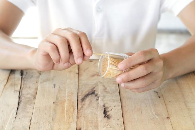 Mujer elegir palillo de madera para limpiar los dientes de la caja de plástico en la mesa de madera
