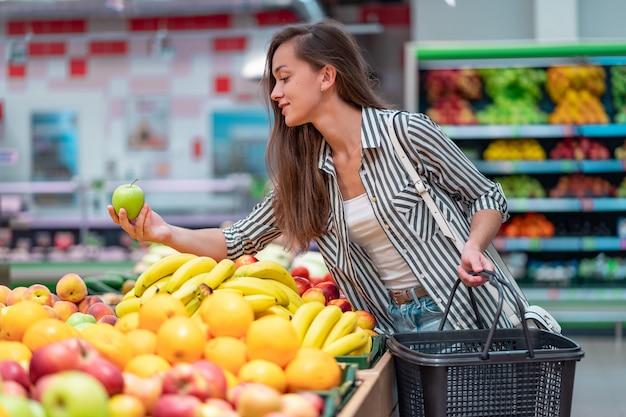 La mujer elige fruta fresca en supermercado. cliente que compra comida en la tienda de comestibles
