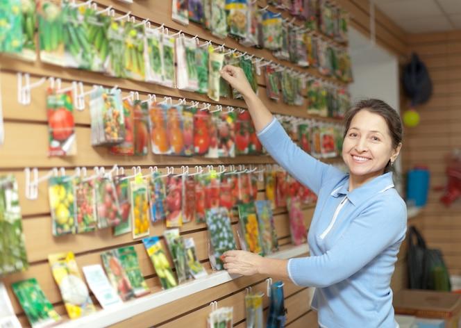 Mujer elige semillas empacadas en la tienda