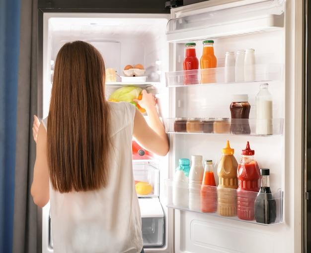 Mujer eligiendo alimentos en el frigorífico en casa