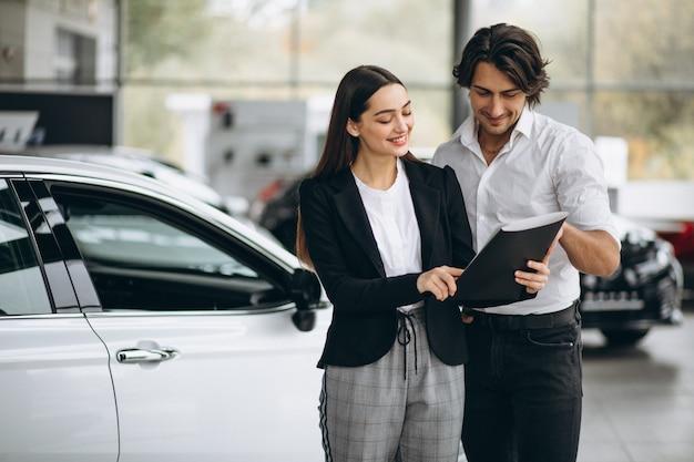 Mujer eligiendo un automóvil en una sala de exposición de automóviles