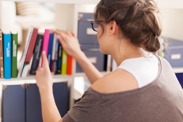 Mujer eligiendo libro favorito de la biblioteca de casa