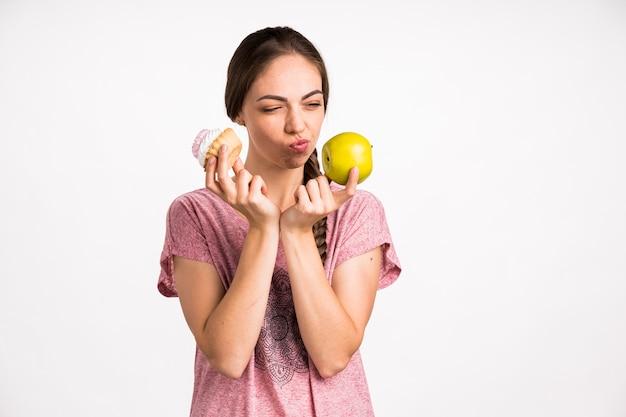 Mujer eligiendo entre manzana y cupcake