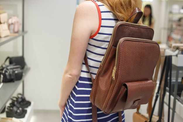 Mujer eligiendo mochila de cuero en la tienda