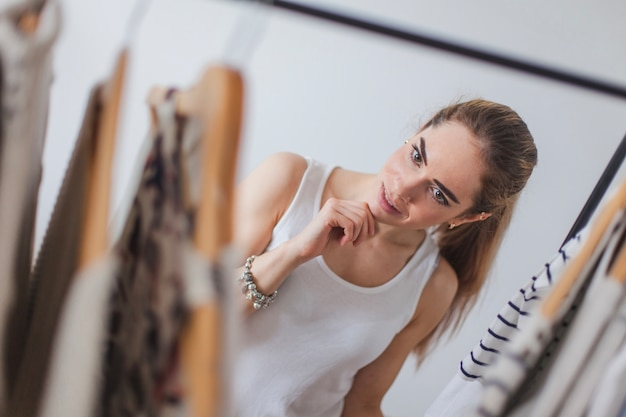 Mujer eligiendo ropa en armario