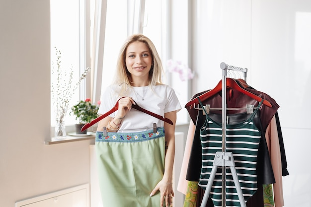 Mujer eligiendo ropa en casa o showroom