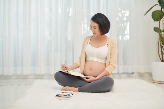 Mujer embarazada acostarse mirando una ecografía