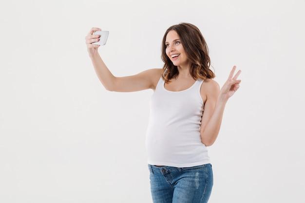 Mujer embarazada alegre hacer selfie con su vientre