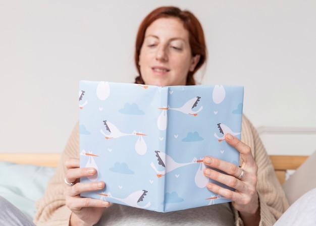 Mujer embarazada de ángulo bajo leyendo libros de bebé
