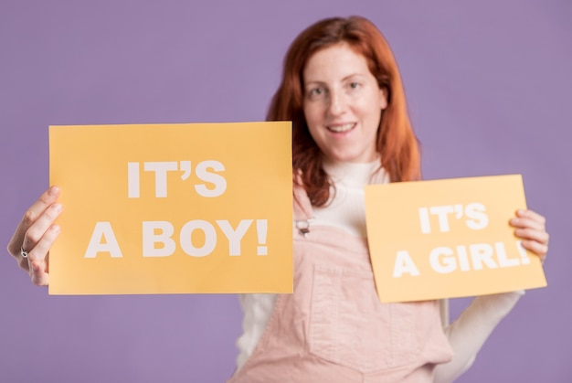 Mujer embarazada de ángulo bajo con papel con género de bebé