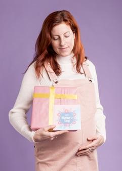 Mujer embarazada de ángulo bajo con regalo y tarjeta de felicitación
