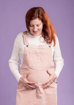 Mujer embarazada de ángulo bajo tocando su vientre