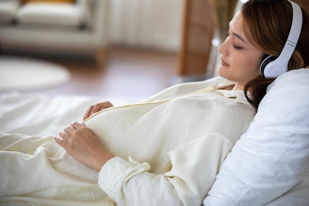 Mujer embarazada asiática escuchando música y cantando y tocando suavemente su barriga, embarazo / parto