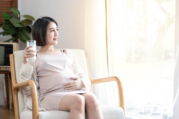La mujer embarazada asiática feliz que toca la panza del vientre que sostiene la leche de cristal en el coche en dormitorio mira por la ventana sonriendo, riendo. disfrutando el concepto de embarazo día de la madre