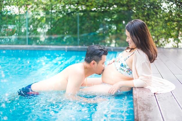 Mujer embarazada asiática con gran barriga. relájese y haga ejercicio en la piscina con su esposo.