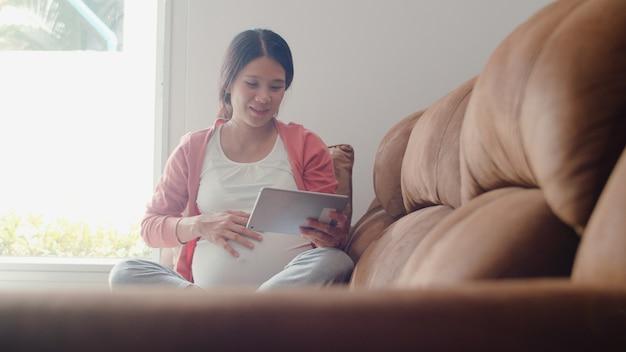La mujer embarazada asiática joven que usa la tableta busca la información del embarazo. mamá se siente feliz sonriendo positiva y pacífica mientras cuida a su hijo acostado en el sofá en la sala de estar en casa.