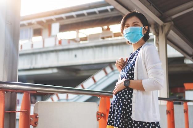 Mujer embarazada asiática en mascarilla en el aeropuerto