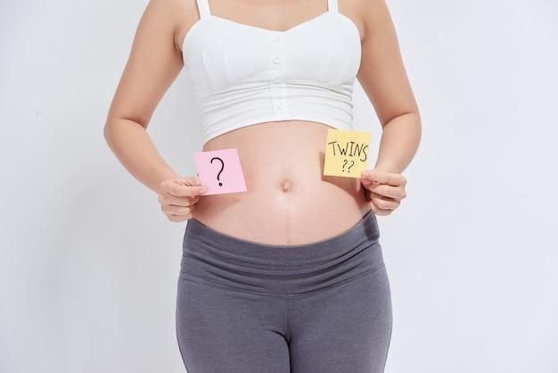 Mujer embarazada asiática con nota adhesiva en su vientre
