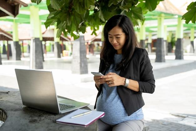 Mujer embarazada asiática en el trabajo usando el teléfono