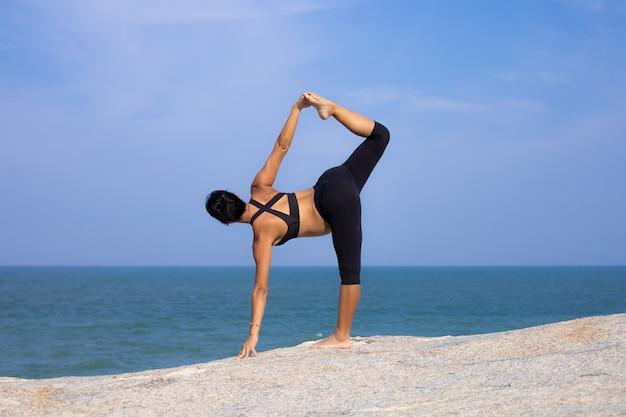 Mujer embarazada asiática yoga en la playa atardecer verano