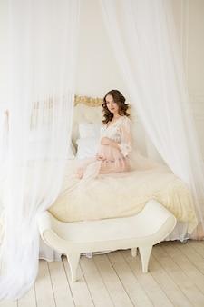 Mujer embarazada en blanco se sienta en la cama