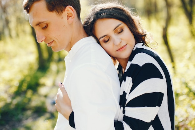 Mujer embarazada brillante y feliz caminando en el parque con su marido