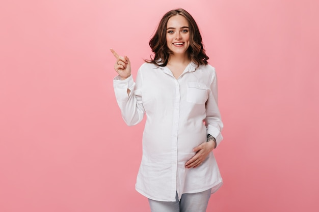 La mujer embarazada de buen humor toca el vientre y sonríe. chica morena con camisa blanca apunta al lugar del texto sobre fondo rosa aislado.
