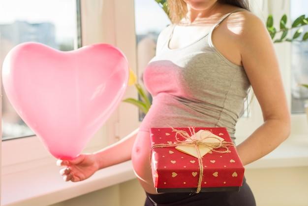 Mujer embarazada con caja de regalo y globo corazón rosa