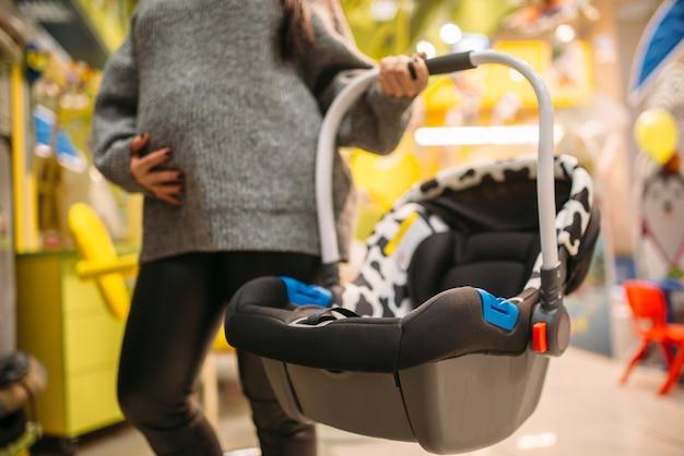 Mujer embarazada con cama portátil en la tienda