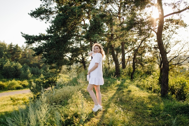 Mujer embarazada caminando en el parque con puesta de sol