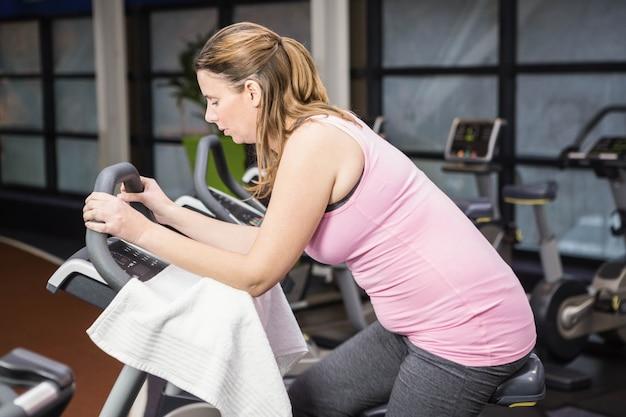 Mujer embarazada cansada en bicicleta estática en el gimnasio