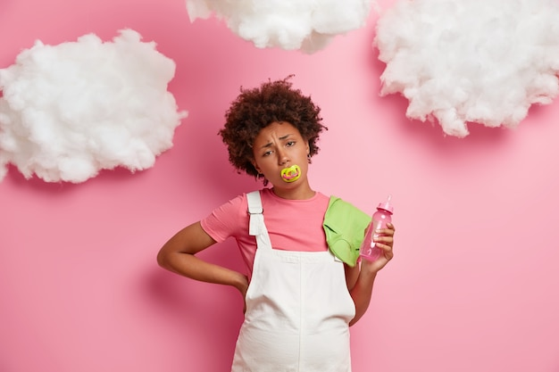 La mujer embarazada cansada sufre dolor de espalda, se para con el vientre de embarazada, sostiene artículos para el bebé, necesita descansar, usa camiseta y sarafan blanco, masajea la espalda, aislado en la pared rosa. futura madre