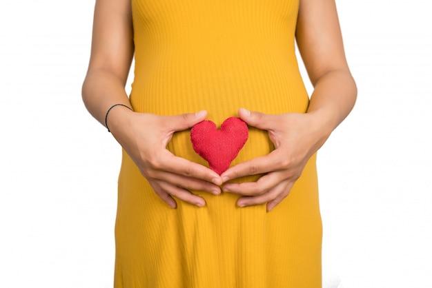 Mujer embarazada con cartel de corazón en el vientre.