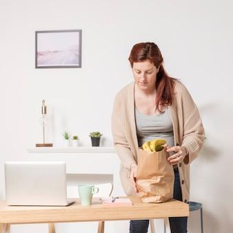 Mujer embarazada en casa con bolsa de supermercado