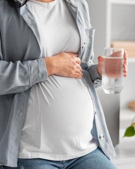 Mujer embarazada en casa sosteniendo un vaso de agua