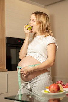 Mujer embarazada comiendo una manzana y midiendo su vientre