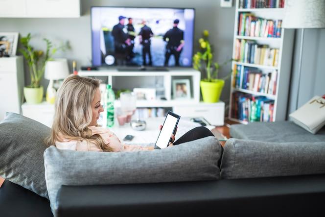 Mujer embarazada con tableta digital en la sala de estar