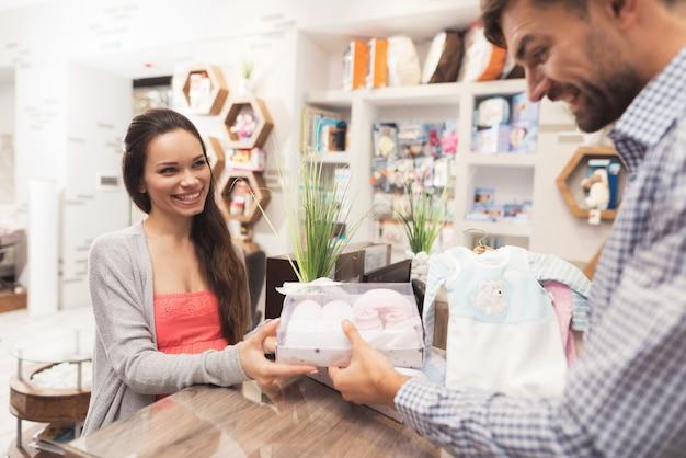 Una mujer embarazada le da dinero a un vendedor en una tienda.