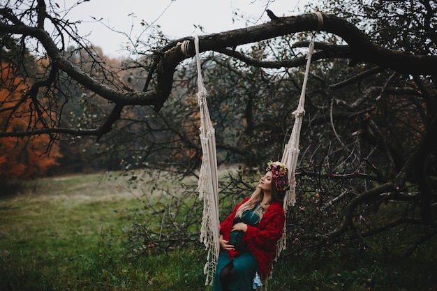La mujer embarazada descansa afuera en el columpio de la cuerda que cuelga en el viejo tr
