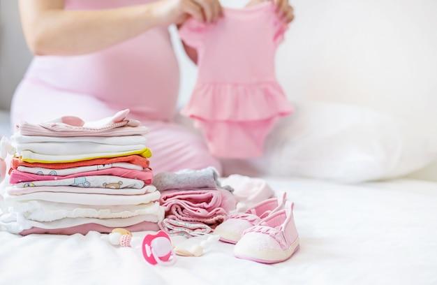 Una mujer embarazada está doblando cosas de bebé