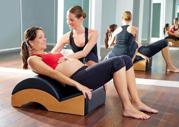 Mujer embarazada ejercicio de pilates roll back