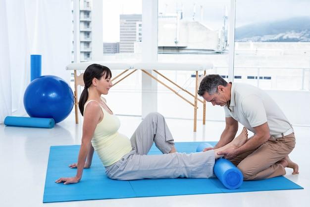 Mujer embarazada ejercitando sus piernas con fisioterapeuta en casa
