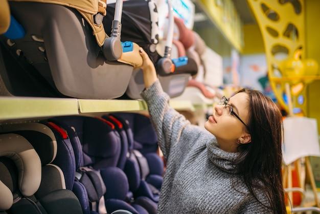 Mujer embarazada elegir asiento de coche para niños en la tienda