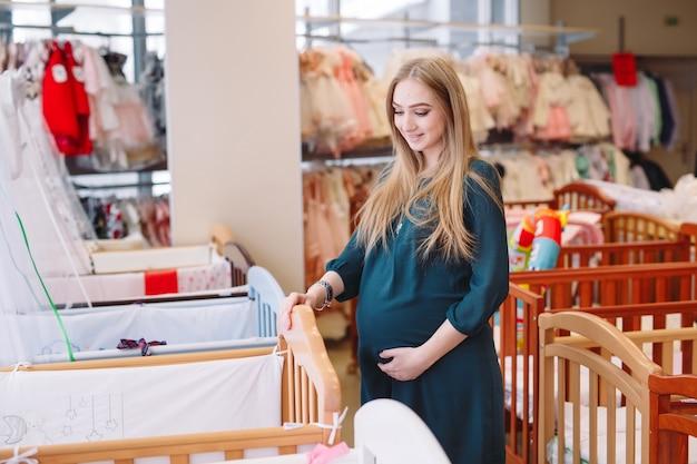La mujer embarazada elige una cuna en la tienda.